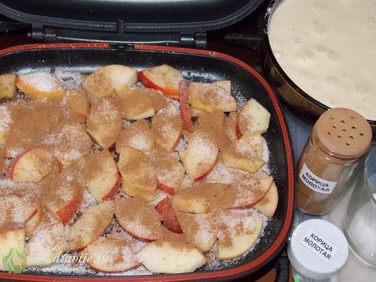 Выложить на одну сторону сковороды все яблоки, посыпать сахаром и молотой корицей