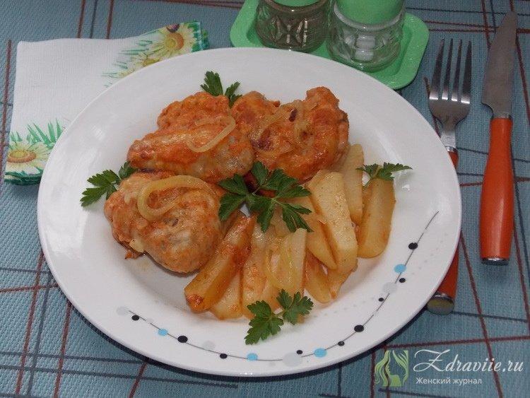 Выложить на тарелку куриные крылышки с картофелем и луком