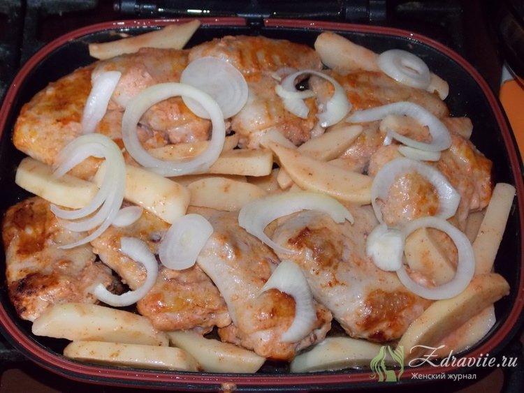 На обжаренные с двух сторон крылья, выложите лук и картофель